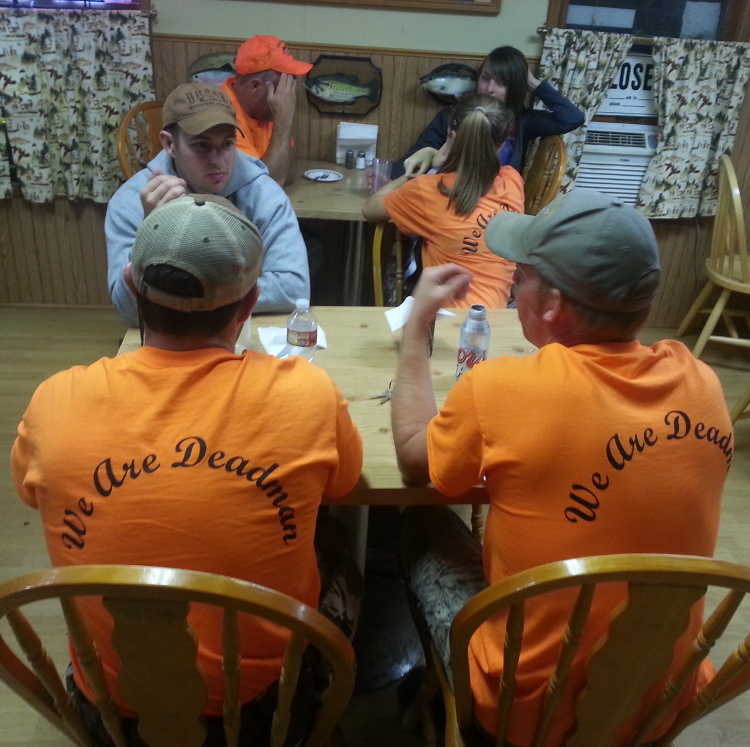 Customers conversing while wearing an orange Deadman Creek Outfitters t-shirt